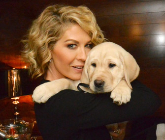 """Jenna Elfman of the NBC series """"Growing up Fisher"""" holds a puppy who will trained to be a guide dog"""