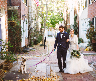 bride and groom outside with a dog on a leash