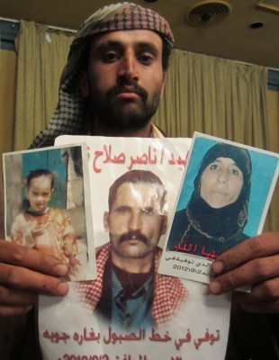 Ahmed al Sabool holds photos of his mother, father and sister, 10. (Letta Tayler/Human Rights Watch).
