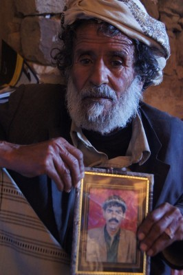 Ahmed Mohammed Al-Shafee' holds a picture of his son, Aaref, who was killed in the strike. (PHOTO: Reprieve)