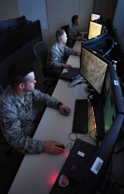 Analysts assigned to the 11th Intelligence Squadron review mission data on Hurlburt Field, Fla., June 11, 2015. The 11th IS executes procession, exploitation and dissemination of day and night imagery intelligence, from manned and unmanned aerial systems. (U.S. Air Force photo/Airman Kai White/Released) (Portions of this image were blurred for security or privacy concerns)