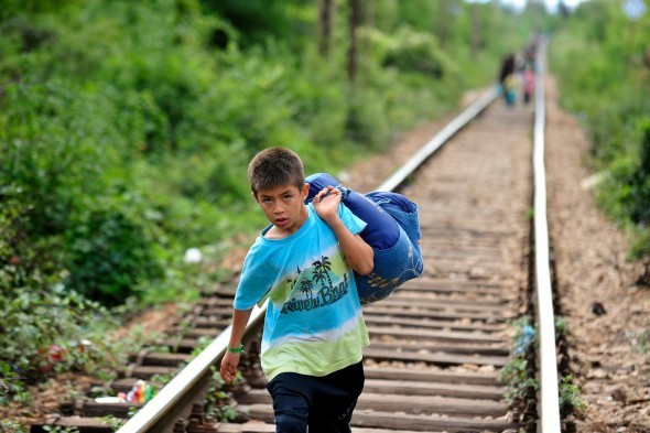 UNICEF/UNI196290/Georgiev A boy carrying his belongings in a large cloth bag over his shoulder is among people walking on railway tracks to cross from the former Yugoslav Republic of Macedonia into Serbia, at the southern town of Preševo, on the border with the former Yugoslav Republic of Macedonia. He is among thousands of refugees transiting Serbia each day with the goal of reaching other countries in the European Union. Many of them have been travelling for more than two weeks after fleeing countries under conflict. Since June 2015, more than 89,160 people have been registered crossing into Serbia, and UNHCR estimates that, at any given time, over 12,000 refugees from the Syrian Arab Republic and other war-torn countries are in Serbian territory. On 11 September 2015, growing numbers of refugees and migrants seeking safety in Europe continue to pass through the former Yugoslav Republic of Macedonia and Serbia. Many of them are fleeing violence, conflict and insecurity in their countries of origin. Since the beginning of the year, over 200,000 refugees – mainly from the Syrian Arab Republic, Afghanistan and Iraq – have transited through both countries with the aim of reaching other European Union countries. Children of all ages and their families, many of them walking and with only the shoes and clothes they are wearing, have been travelling for days. They are physically exhausted, dehydrated, sunburnt or wet and cold as a result of extreme temperatures and inclement weather, and in urgent need of safe drinking water, food, shelter, hygiene facilities and medical assistance. Between 1 and 6 September, nearly 10,000 people – about 40 per cent of whom are children and women – crossed from Greece into the former Yugoslav Republic of Macedonia (at the southern border city of Gevgelija), and more than 7,720 people crossed into Serbia through Preševo, the southernmost town and municipality bordering the former Yugoslav Republic of Macedonia. In response to the crisis, UNICEF, workin