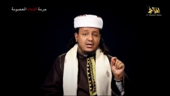 Sheikh Harith al Nadhari, Al Qaeda in the Arabian Peninsula's leading spokesman, preacher and propaganidst, sits before a black background in a white hat and black robe. He is emphasising a point with his hadn.