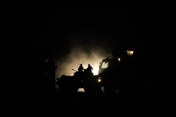Ugandan soldiers, belonging to the African Union Mission in Somalia, sit on top of a tank in the early morning hours before advancing on the town of Qoryooley, Somalia, on March 22. AU UN IST PHOTO / Tobin Jones