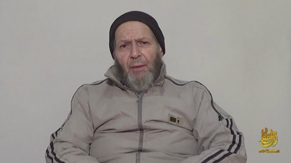 Warren Weinstein sits in front of a grey background in this still from an al Qaeda propaganda video. He wears a grey tracksuit and black hat.