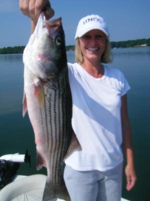 Mooresville, NC resident Michele Smith holds a Striped Bass caught on Lake Norman while fishing with her dad, Paul Atkins and Capt. Gus Gustafson