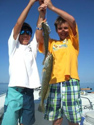 Alex Meeks (L) and fishing buddy, Logan, (R) of Bartow with a pair of trout caught on a tandem rig while fishing with Capt. Ray Markham aboard the Flat Back II out of Terra Ceia.<br>