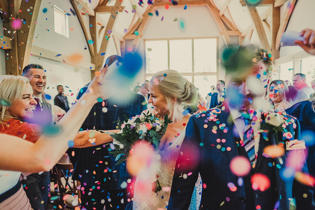 mill barns wedding photographer, mill barns wedding photography, shropshire wedding photographer, manchester wedding photographer, manchester wedding photography, ayesha photography, creative manchester wedding photographer, mill barns wedding, wedding at mills barn, colourful confetti as bride and groom walk back down the aisle