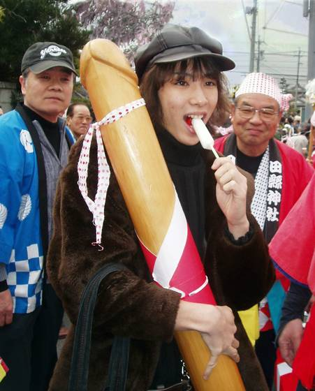Girl_poses_with_wooden_phallus_at_tagata-honen_festival