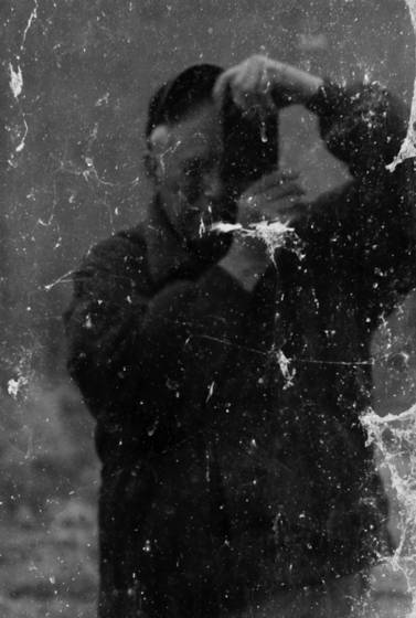 Self_portrait_in_a_dirty_window