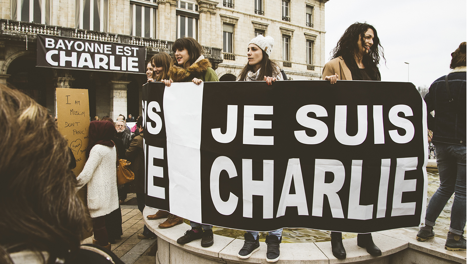 Protesters hold up Je Suis Charlie banner after Charlie Hebdo terrorist attack.