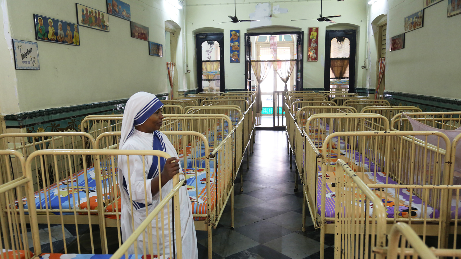 Indian nun stands in an orphanage surrounded by cribs.
