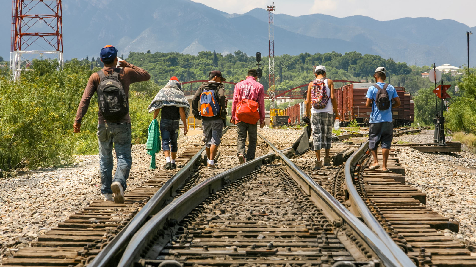 Migrants crossing train tracks.