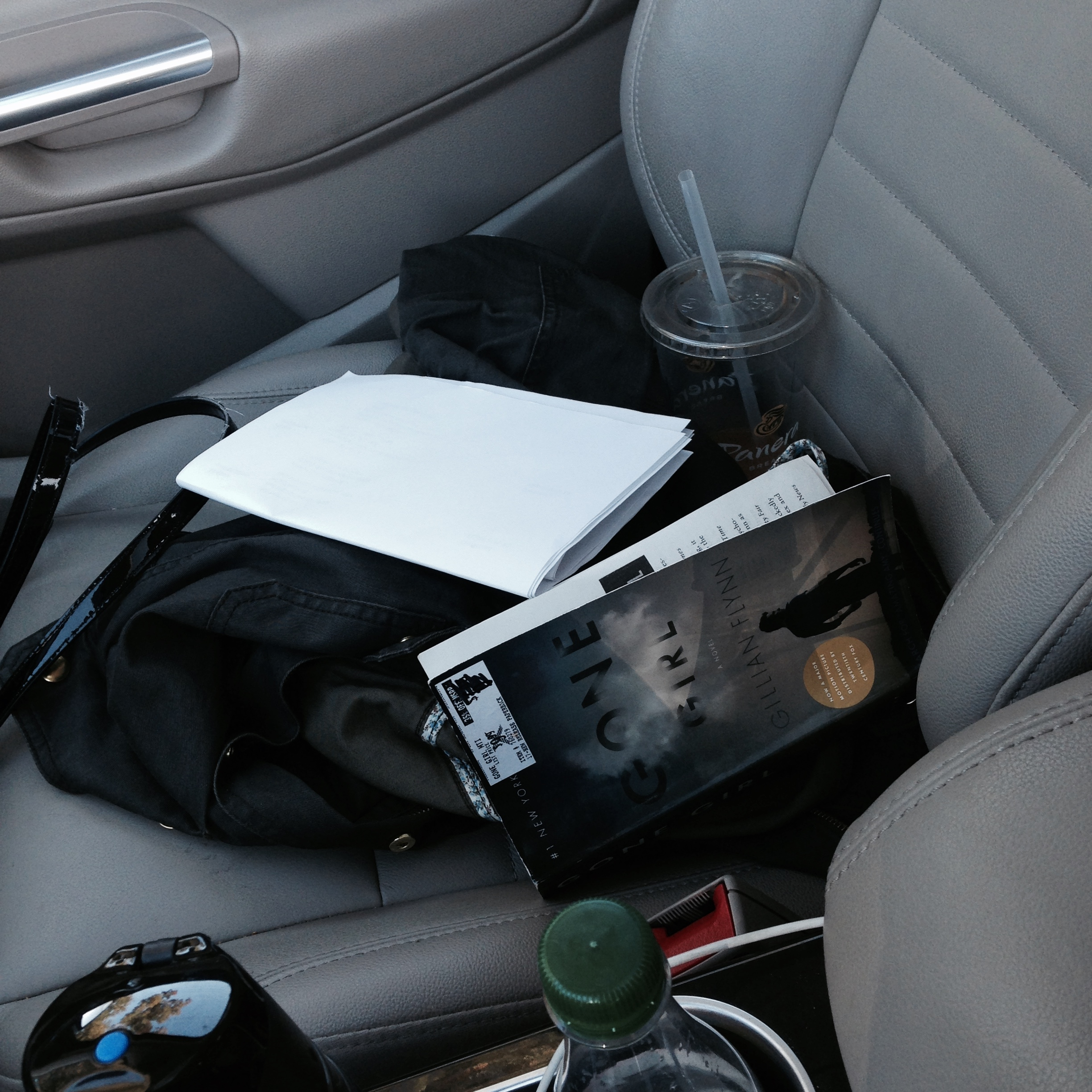 The passenger seat of my car, complete with multiple water bottles, empty iced coffee cups and my schedule for the day
