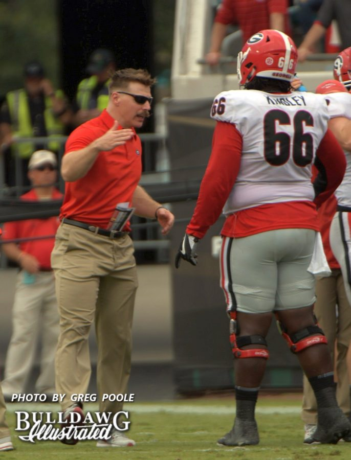 """Georgia's assistant strength and conditioning coach, Aaron Fields, is there to give Solomon Kindley (66) a """"that a boy."""" - Georgia-Florida, Saturday, Oct. 28, 2017 -"""