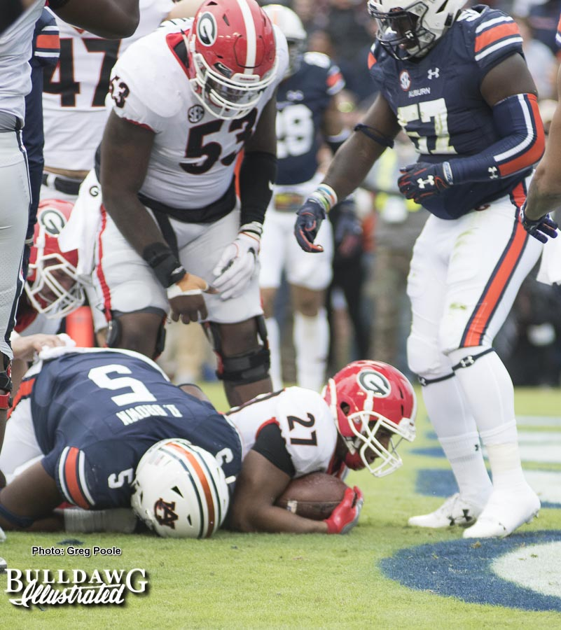 Nick Chubb (27) punches the ball across the goal line to give Georgia a touchdown in the first quarter. - UGA vs. Auburn, Sat., Nov. 11, 2017 -