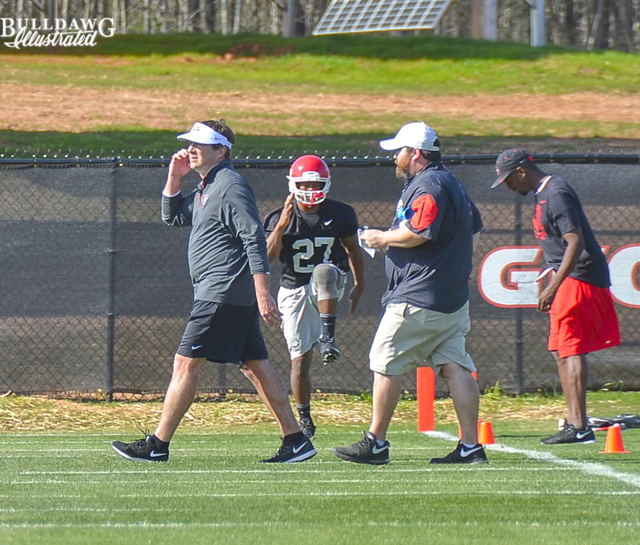 Kirby Smart takes a call while Nick Chubb works out
