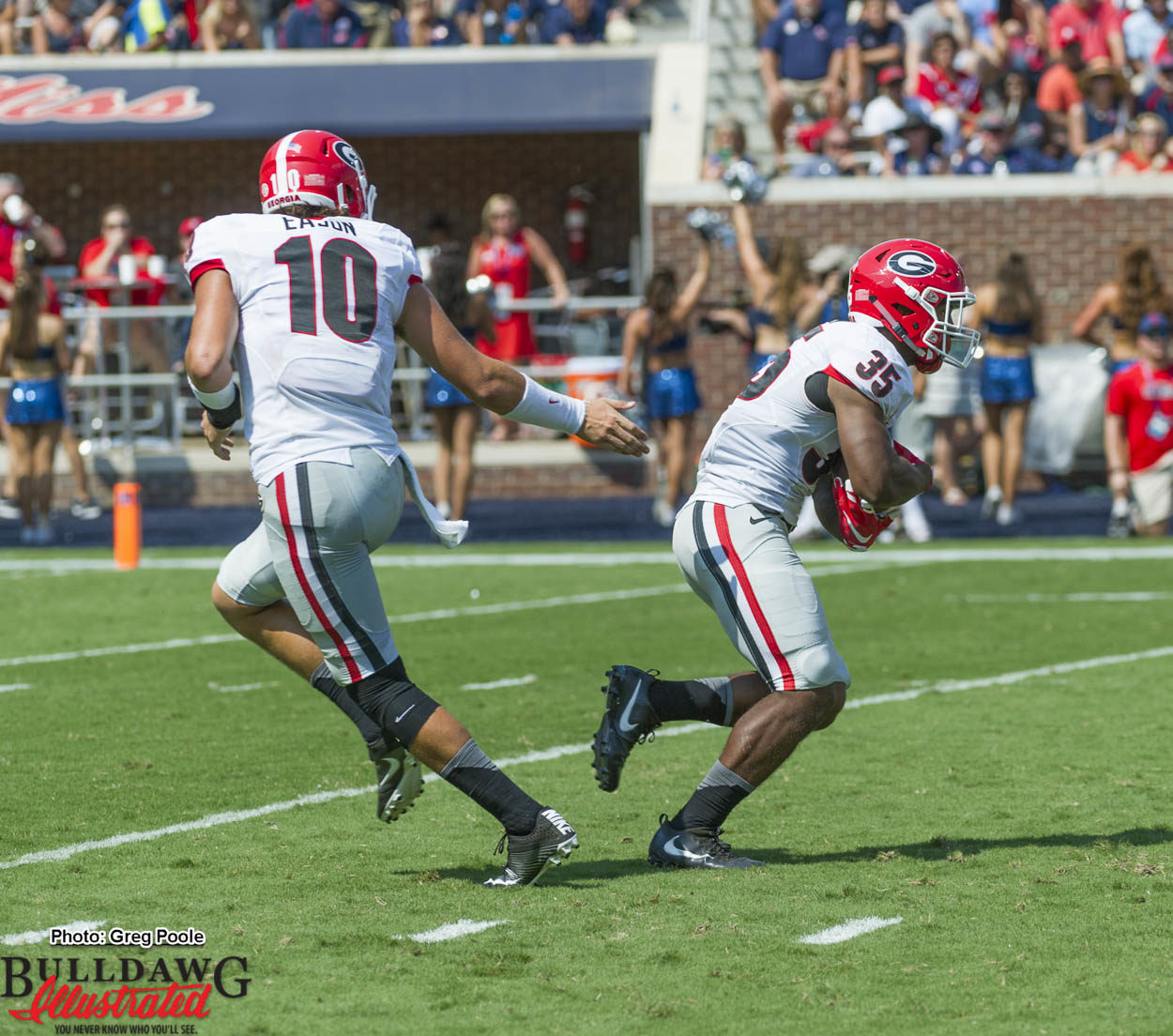 Jacob Eason (10) hands off to Brian Herrien (35)