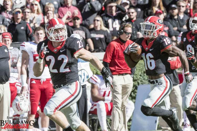 Brendan Douglas (22) leads the way for Isaiah McKenzie (16) during a punt return
