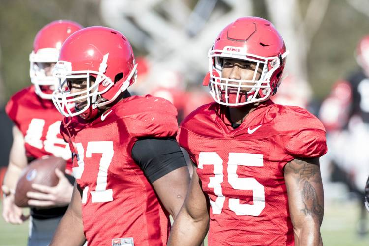 Nick Chubb (27) and Brian Herrien wait to run a drill during practice.