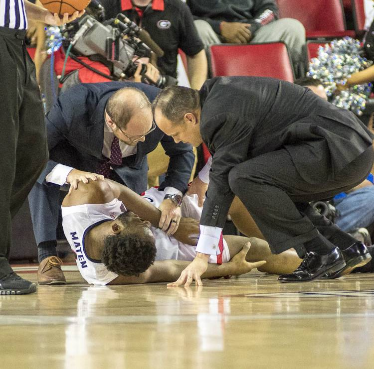 Coach Mark Fox and staff console Yante Maten (1) after he goes down with a leg injury early in the game versus Kentucky