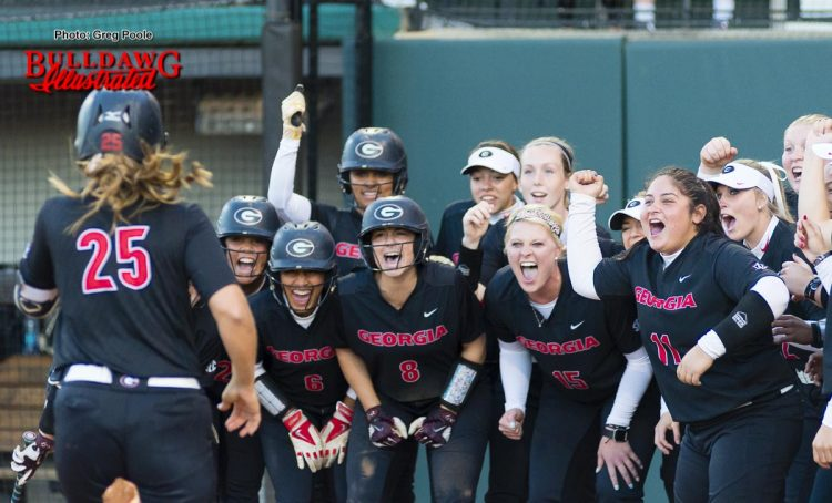 Lacey Sumerlin is met at home plate by her teammates to celebrate her grand slam home run