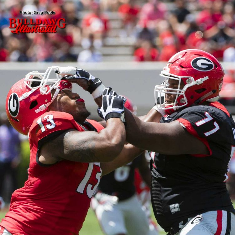Isaiah Wynn (77) assists Jonathan Ledbetter (13) with removal of his helmet – G-Day 2017