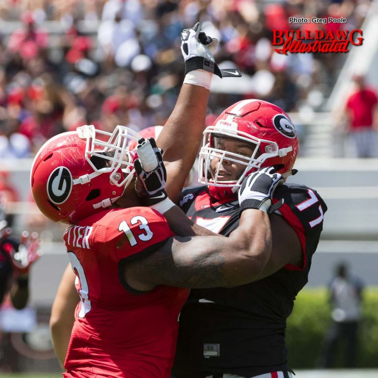 Isaiah Wynn (77) with hands to the face of Jonathan Ledbetter (13)