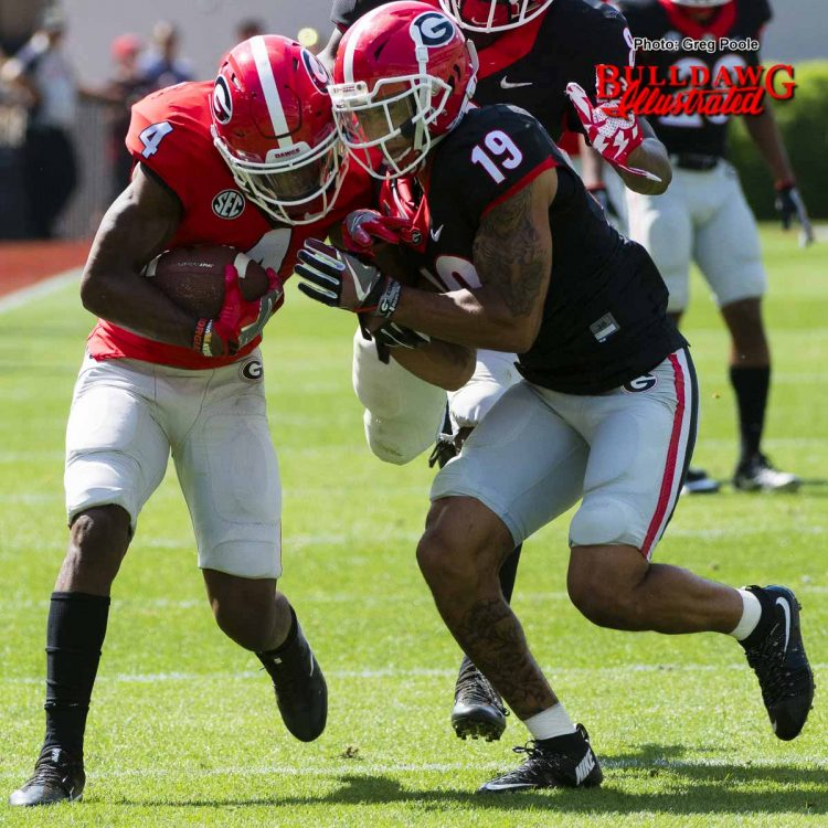 Mecole Hardman (4) fights SS Jarvis Wilson (19) for extra yards