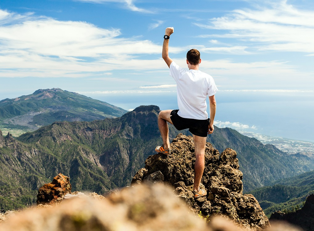 man standing on mountaintop with fist in air