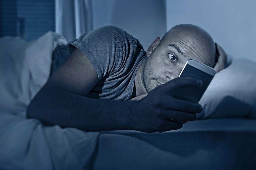 Man using phone in bed