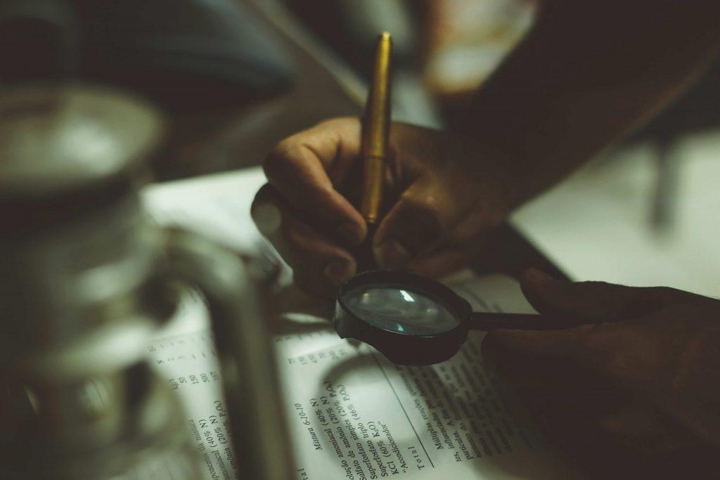 pessoa lendo livro com lupa
