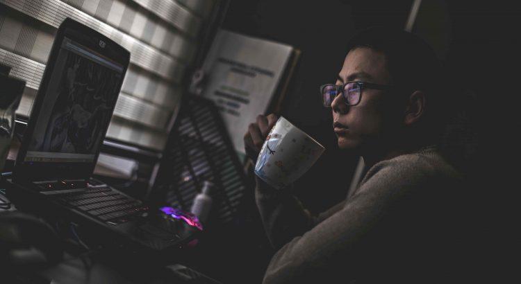 homem oriental olhando para o computador