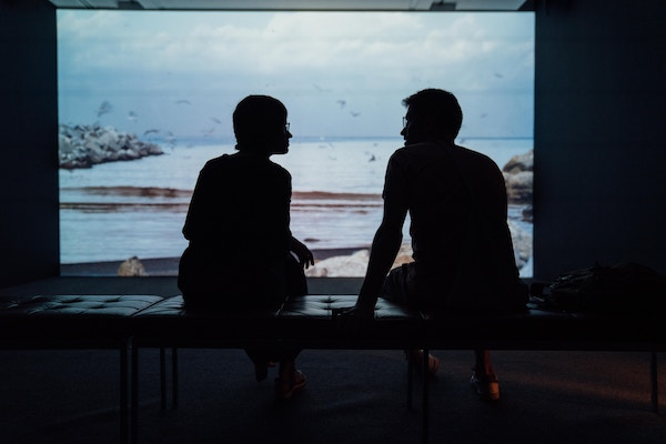 Two people in silhouette, having a conversation