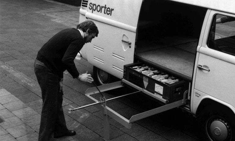 Ingeniero de Volkswagen colocando paquete de pilas dentro de cajuela de Combi Elektro Transporter