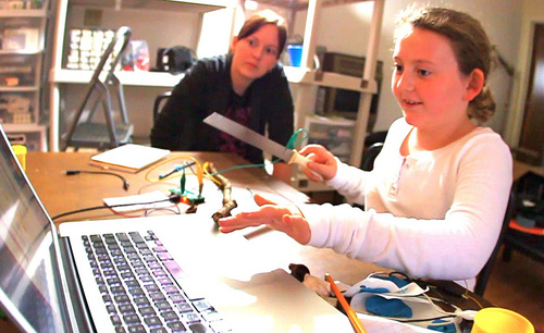 A girl using Makey Makey