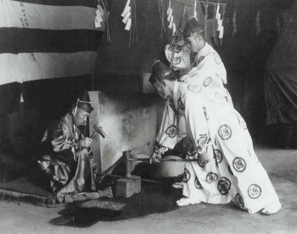 Kuninobu forging swords with Masahiro as sakite (hammer-man) in the rear right of the picture