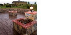 Stamped Concrete, stone sitting walls, outdoor kitchen, gable roof covered composite screened deck, lights, water feature