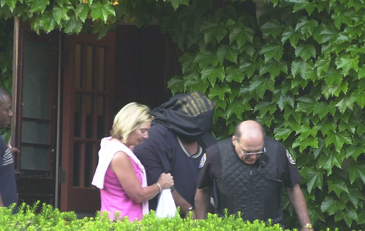 Joe Traver, center, has his face covered by a shirt as he is escorted out of his home on Hodge Avenue by Erie County Sheriff's Chief Patricia Bowers, left, and another officer on June 12, 2001.  A sheriff's deputy was injured as Traver was being arrested when another officer's firearm accidentally discharged. (Buffalo News file photo)