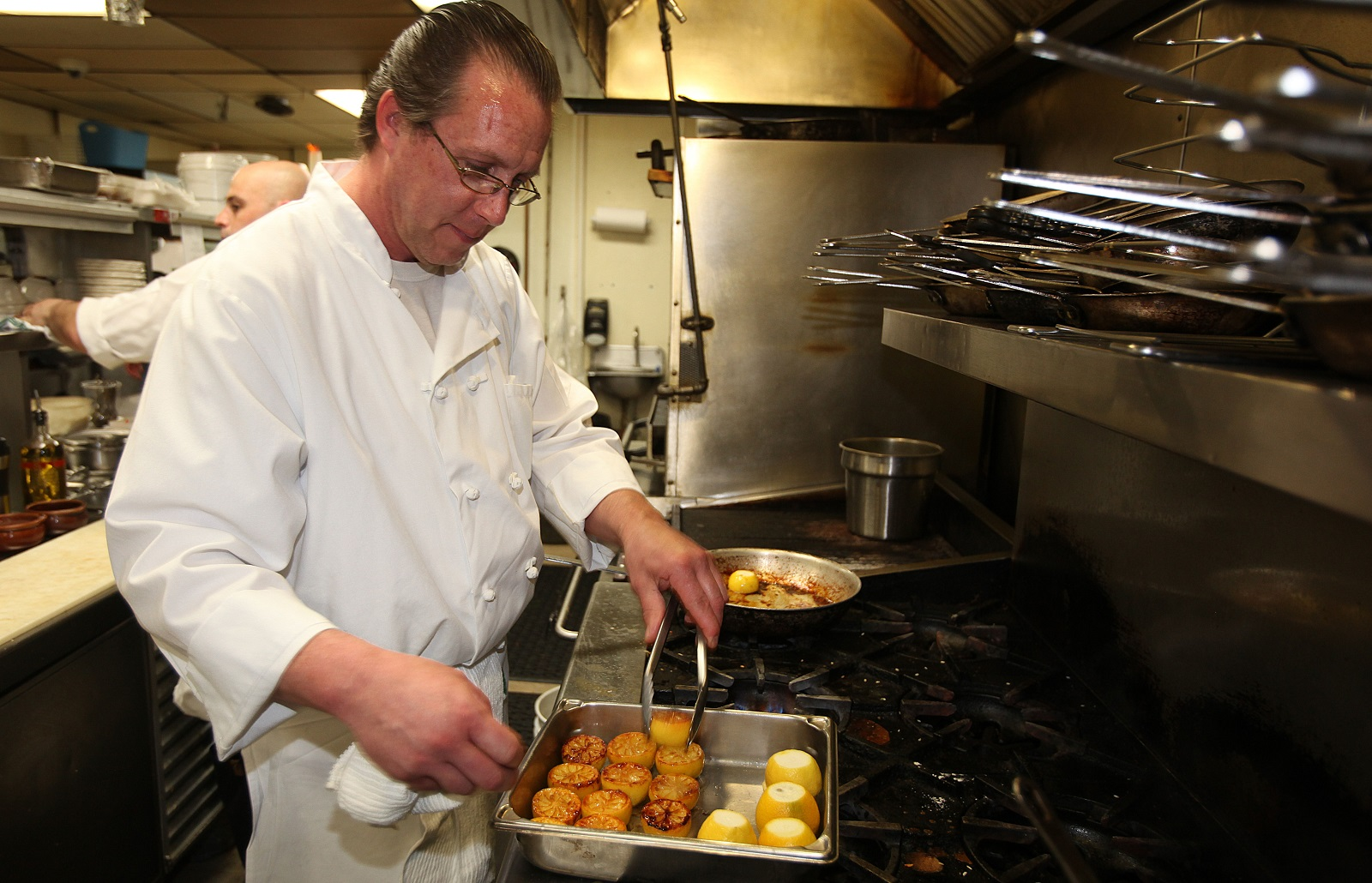 Saute Chef Daryl Rogowski caramelizes lemons in the kitchen at Protocol Restaurant. (Buffalo News file photo)