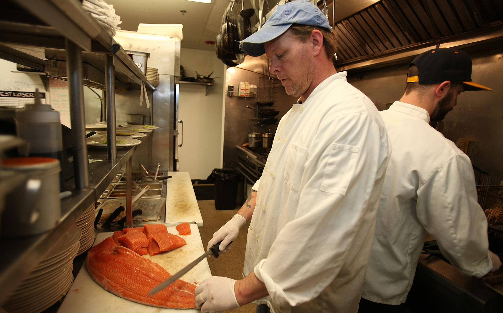 Chef Jerry O'Neill cuts up salmon in the kitchen at Hideaway Grille. (Buffalo News file photo)