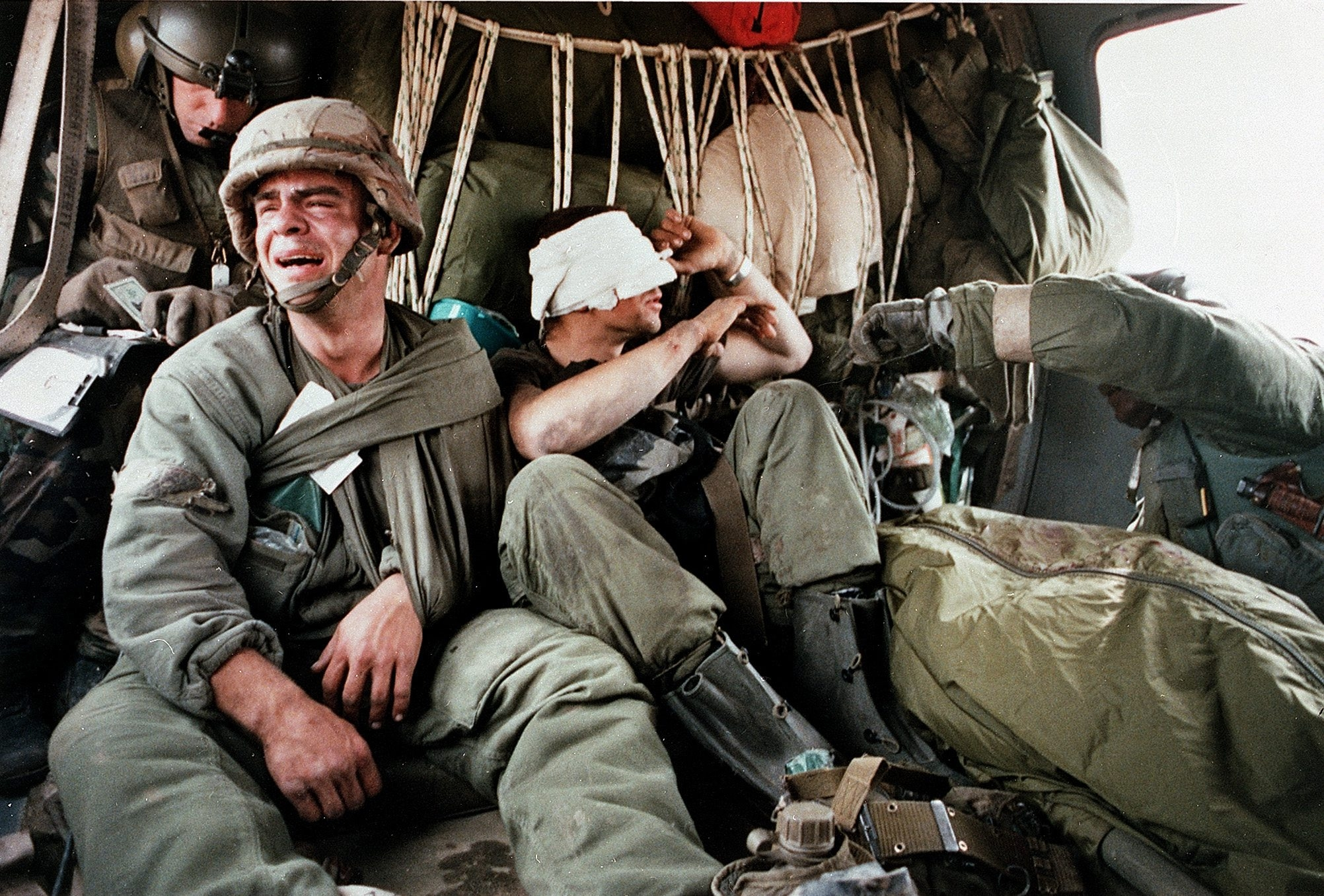 A wounded Sgt. Ken Kozakiewicz sobs as Cpl. Mike Tsangarakis peers into the bodybag holding their comrade, Pvt. Andy Alaniz. (David C. Turnley photo)