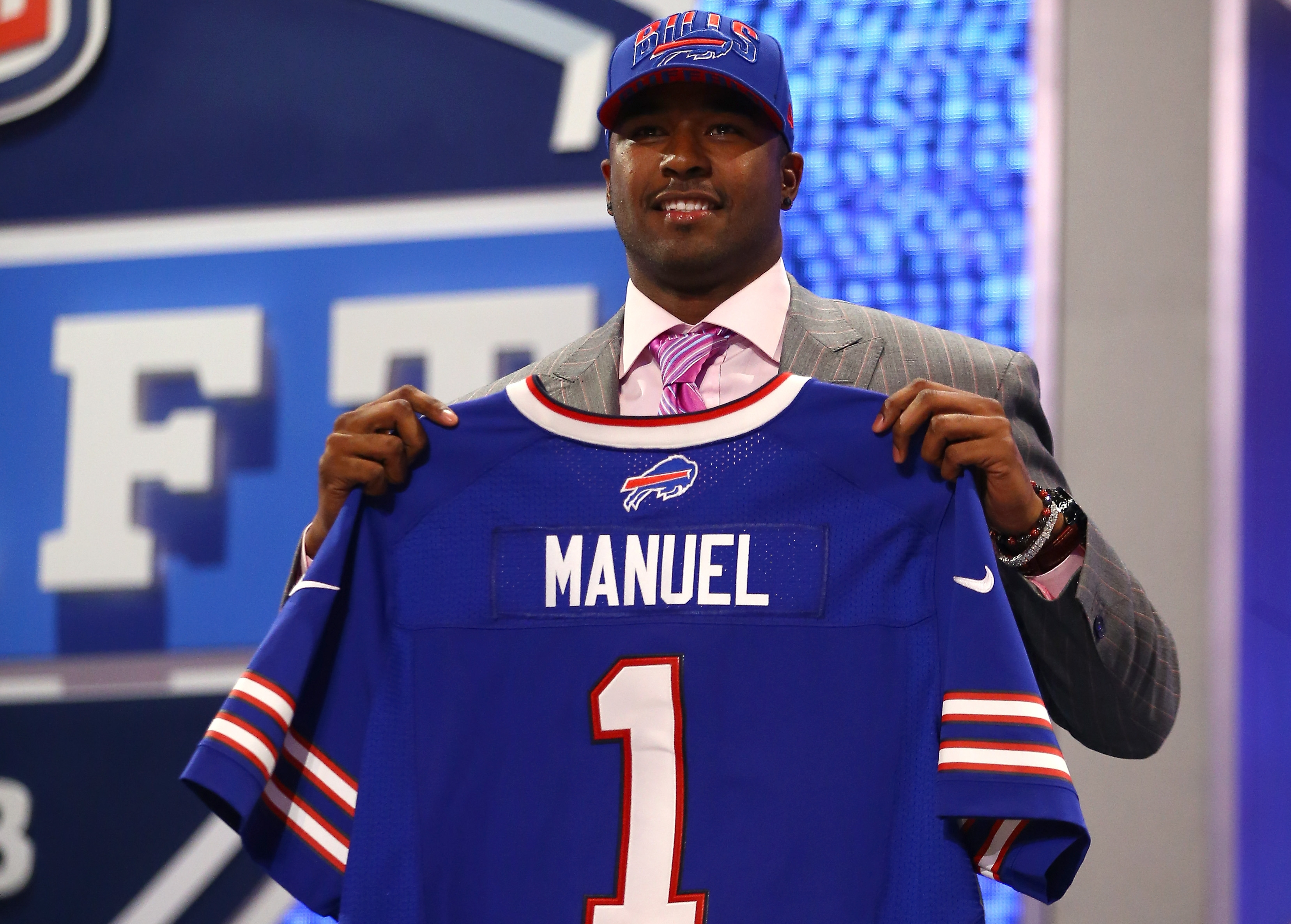 E.J. Manuel of the Florida State Seminoles holds up a jersey on stage after he was picked #16 overall by the Buffalo Bills in the first round of the 2013 NFL Draft at Radio City Music Hall on April 25, 2013 in New York City.  (Photo by Al Bello/Getty Images)