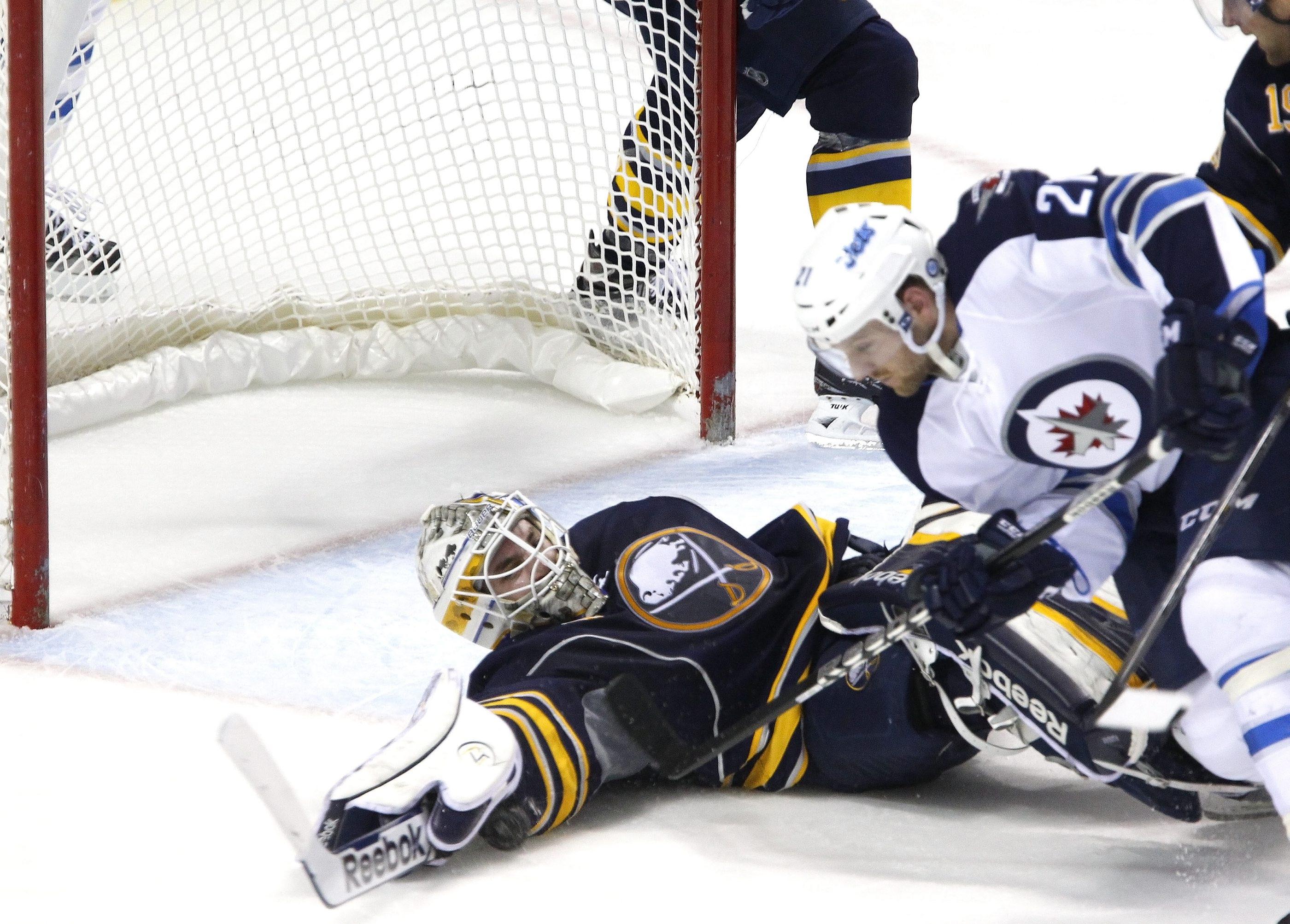 Buffalo goaltender Jhonas Enroth makes a sprawling save against Winnipeg's Aaron Gagnon during Monday night's 2-1 loss.