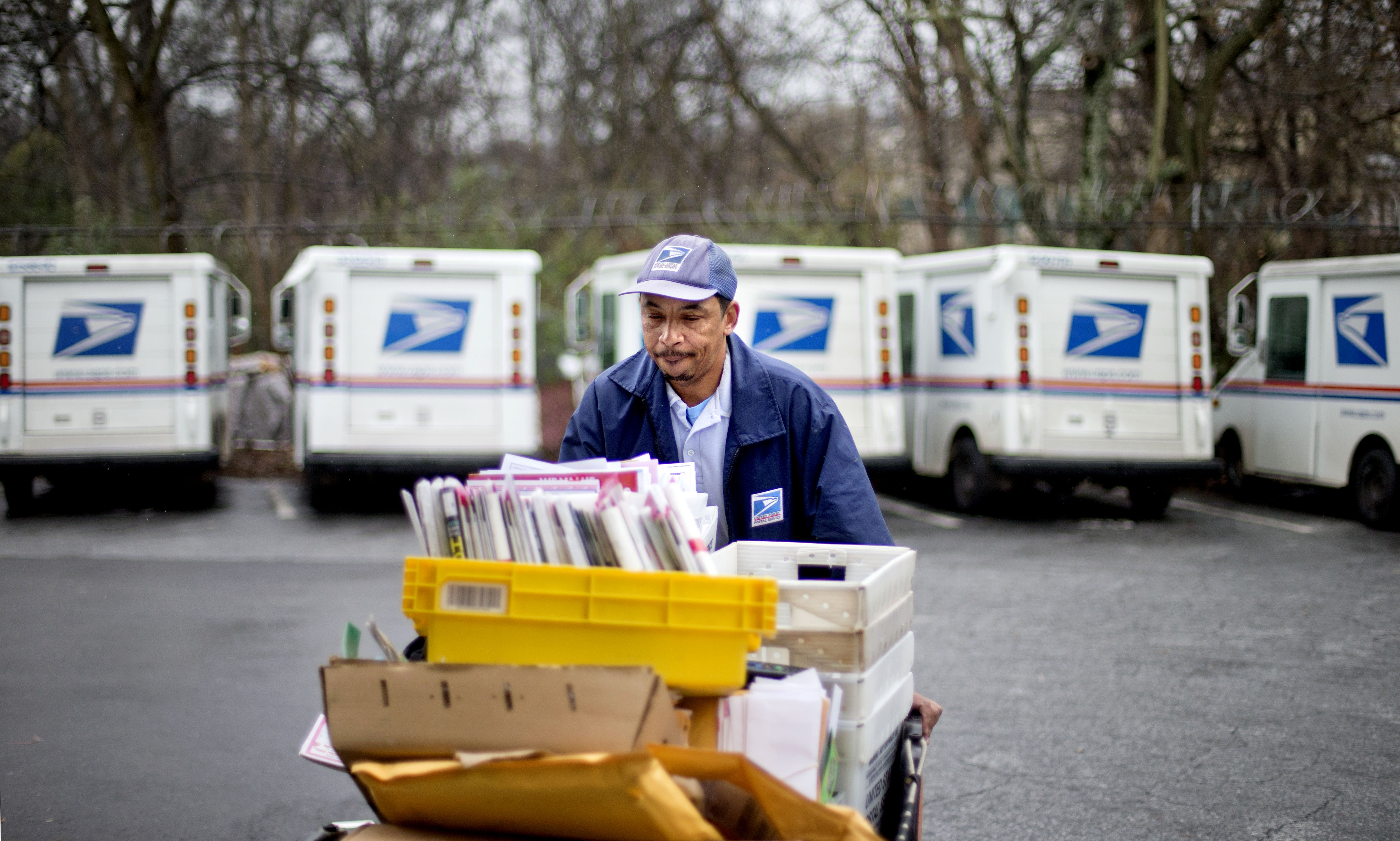 FILE - In this Feb. 7, 2013 file photo, U.S. Postal Service letter carrier Michael McDonald gathers mail to load into his truck before making his delivery run in the East Atlanta neighborhood, in Atlanta. The U.S. Postal Service says it will delay plans to cut Saturday mail delivery because Congress isn't allowing the change. The Postal Service said in February that it planned to cut back in August to five-day-a-week deliveries for everything except packages, as a way to hold down losses. (AP Photo/David Goldman)