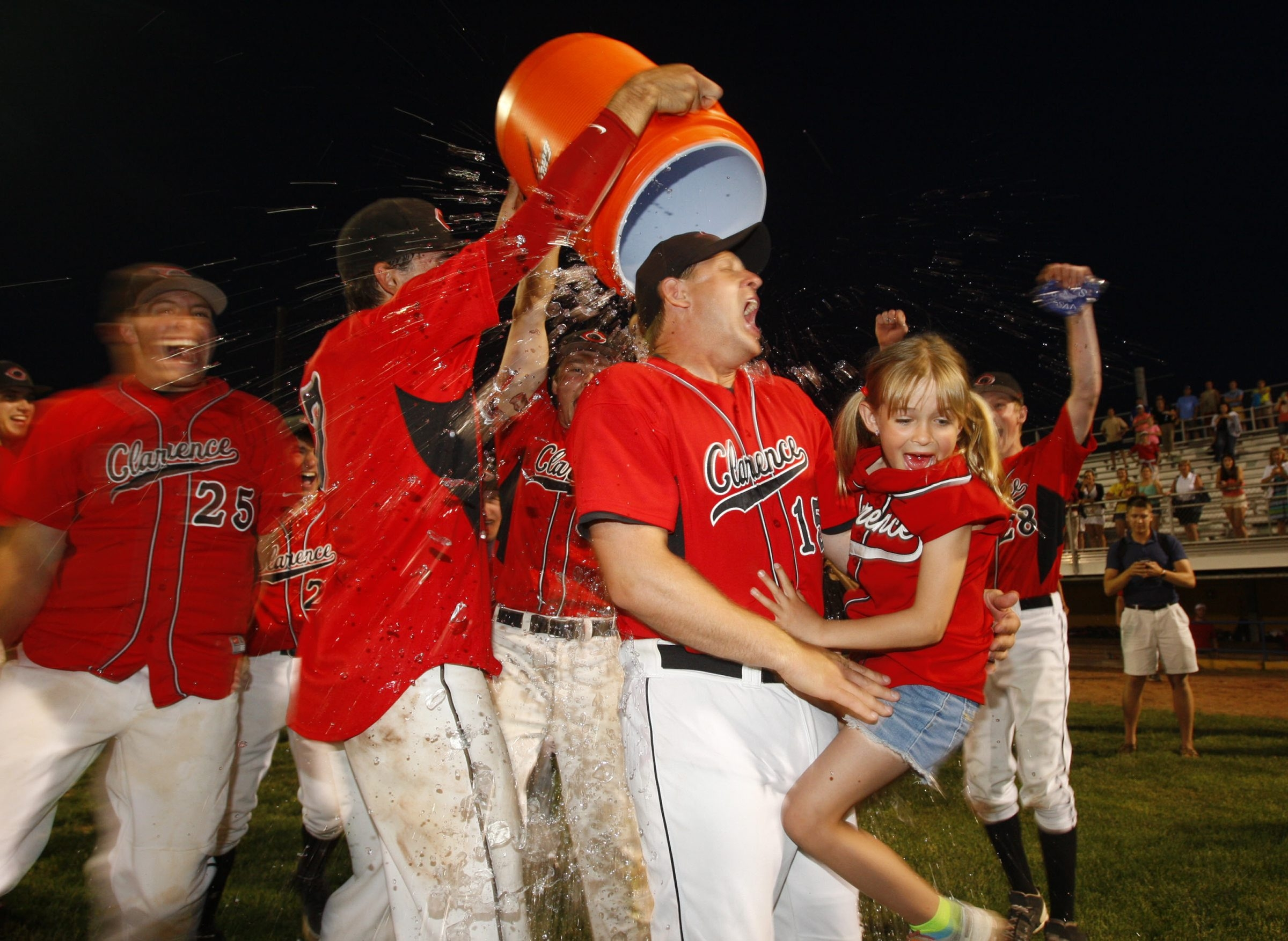 Clarence coach Dave Smith holds his daughter Kiersten as his team dumps water on him to celebrate the Red Devils' 2-1 win over Lancaster.