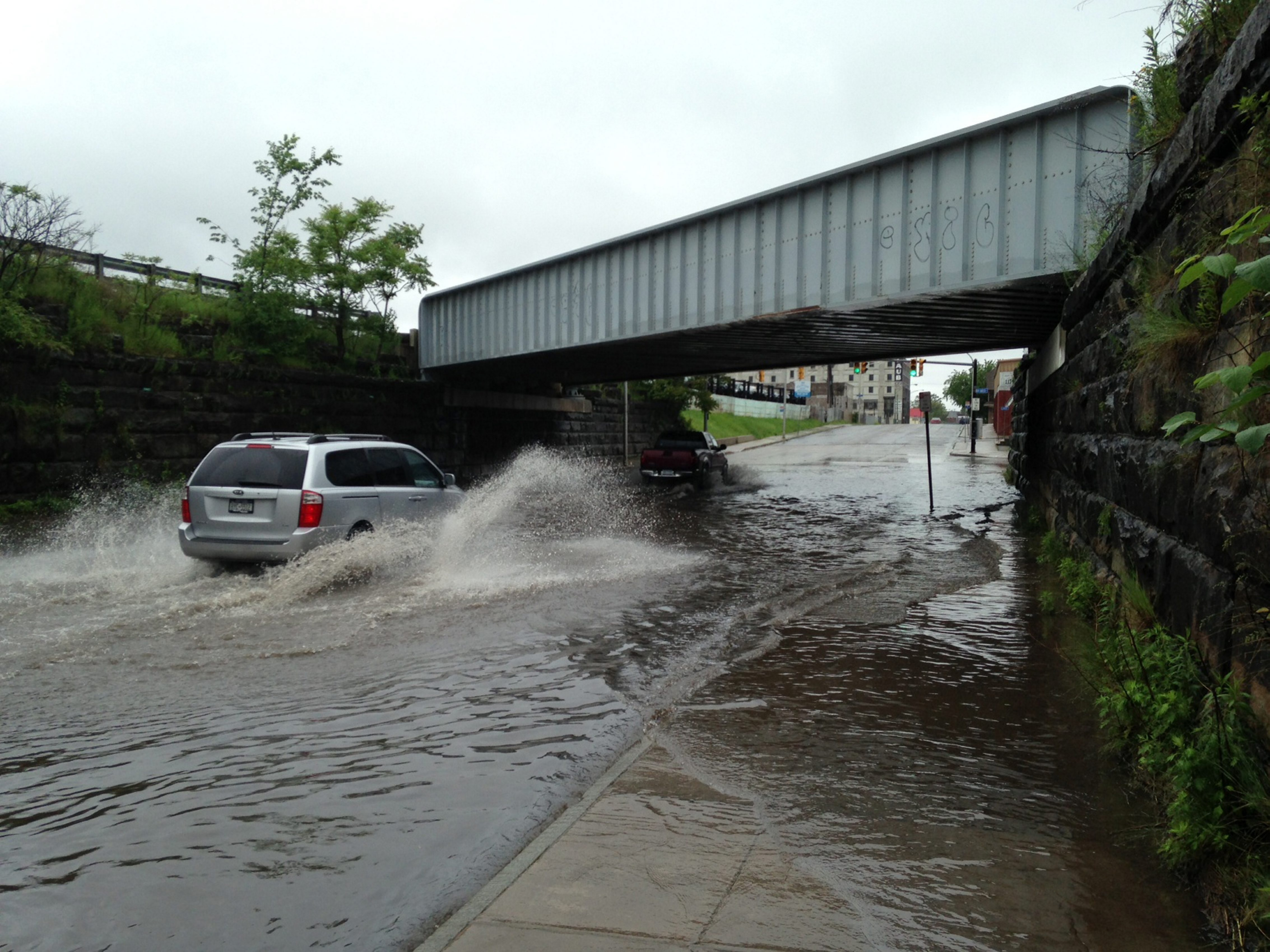 A car navigates flooded area under the train bridge on Clinton Street in Buffalo today. (Photo by Robert Kirkham)