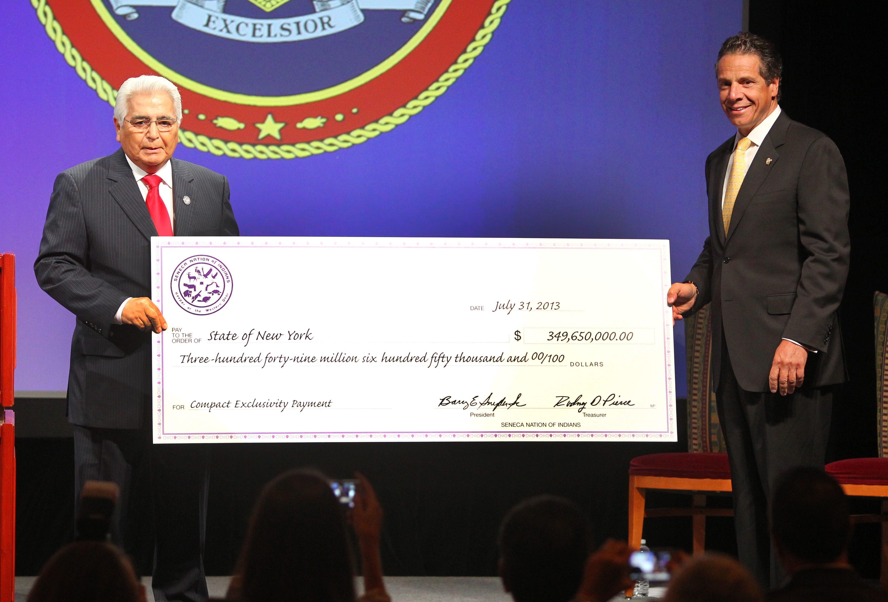 Seneca President Barry Snyder gives a $349 million dollar check to Gov. Andrew Cuomo at the Seneca Niagara Casino in Niagara Falls Wednesday, July 31, 2013.  (Mark Mulville/Buffalo News)