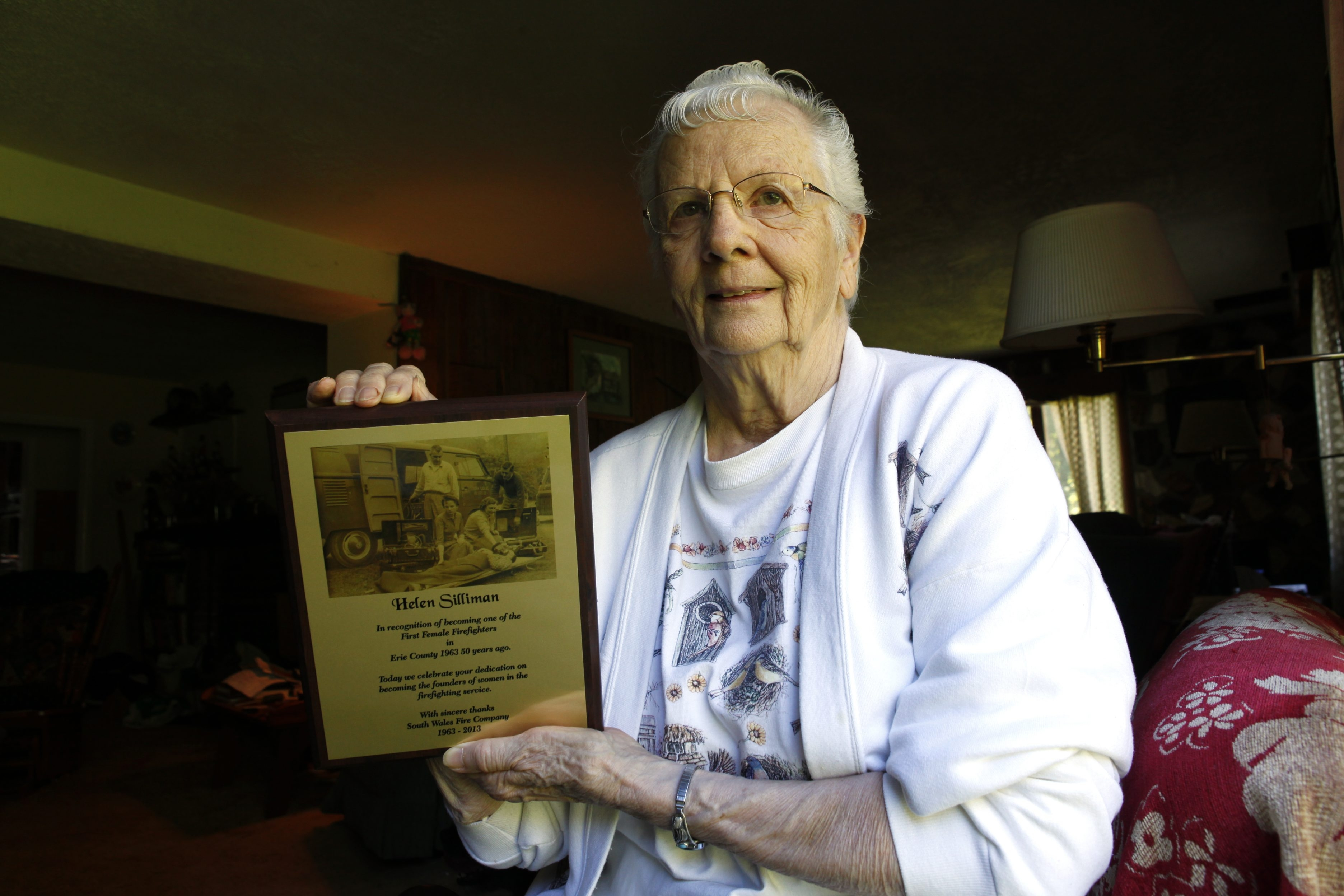 Helen Silliman displays plaque she received as tribute for her being, with the late Florence Bragg, one of Erie County's first two female firefighters.