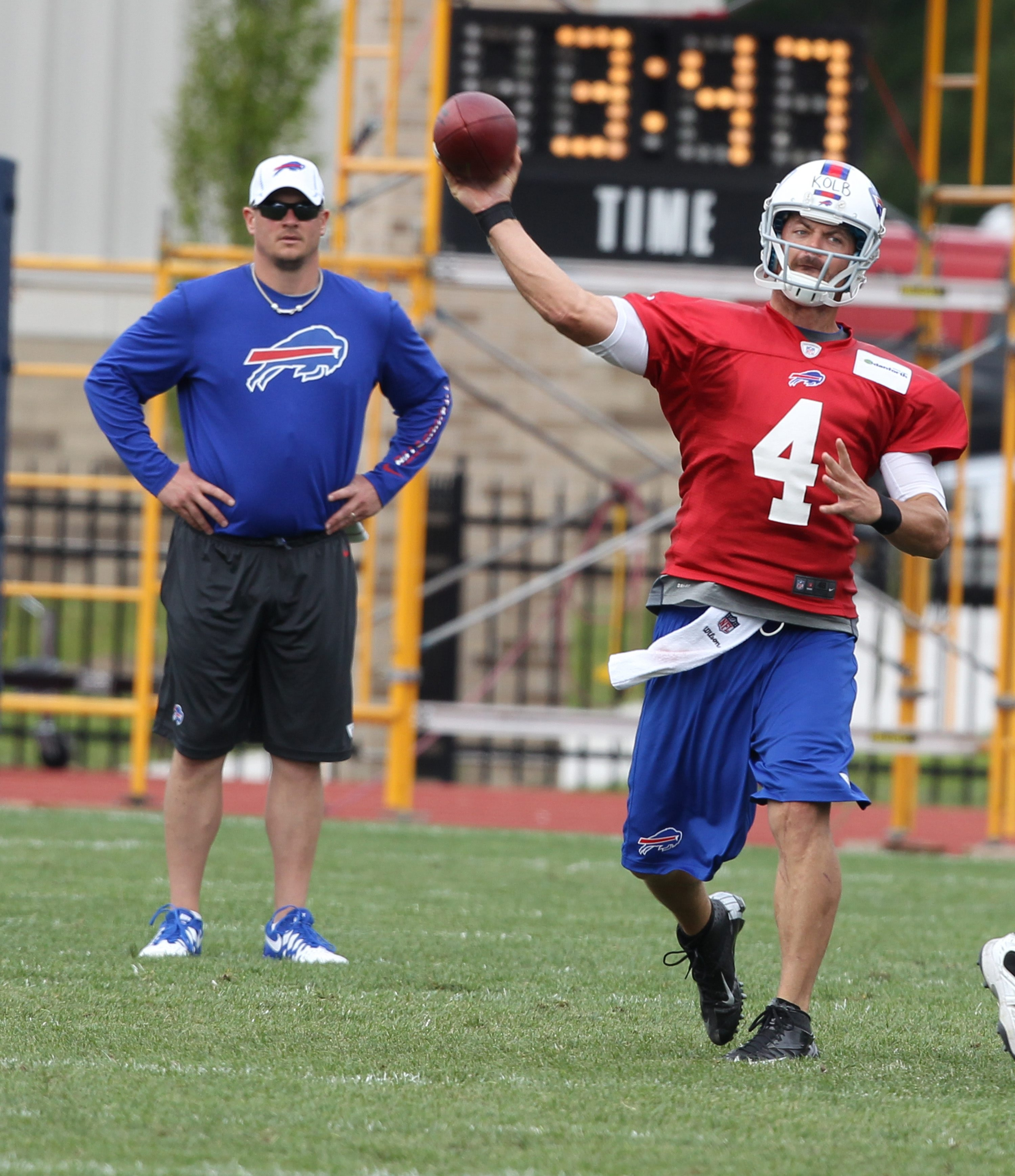 Buffalo Bills quarterback Kevin Kolb throws during practice under the watchful eye of offensive coordinator Nathaniel Hackett on Monday.